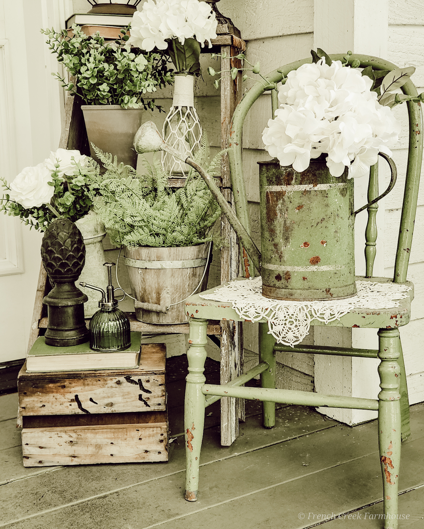 This springtime front porch vignette features a vintage watering can, chippy green chair, rustic old stepladder, and loads of spring florals