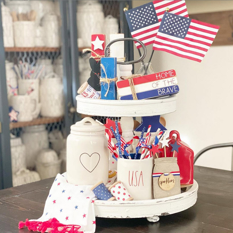 A two-tier white tray with Rae Dunn decor for 4th of July